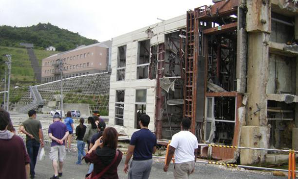 Students walk past a three-story concrete building in Onagawa tipped by the tsunami, whose waters reached the red-brick hospital at left.
