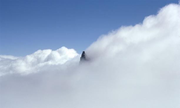 Little Tahoma, a satellite peak of Mount Rainier, poking through the clouds.