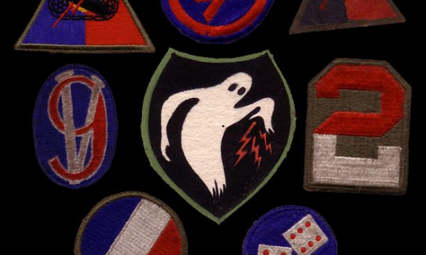 Uniform markings were adopted as well. A sampling of patches worn by Ghost Army members, along with the Ghost Army logo at center.