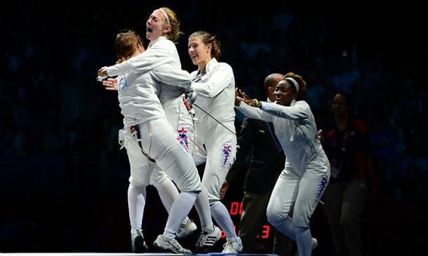 Aug. 4: Susie Scanlan '14, second from left, and Maya Lawrence '02, right, joined the celebration after Courtney Hurley, left, scored a touch in overtime to lead the United States over Russia in the women's team epee bronze-medal match.