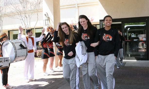 From left, Blake Dietrick '15, Jess Shivers '15, and Mariah Smith '15 get a rousing sendoff from the team hotel, thanks to the Princeton cheerleaders and band.