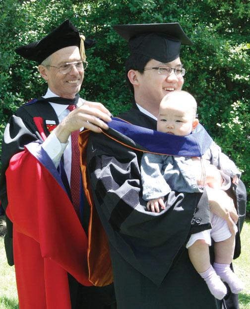 Dean of the Graduate School William B. Russel hoods Edmond Choi *13 — along with Choi's 5-month-old daughter, Stephanie — at a reception after Commencement.