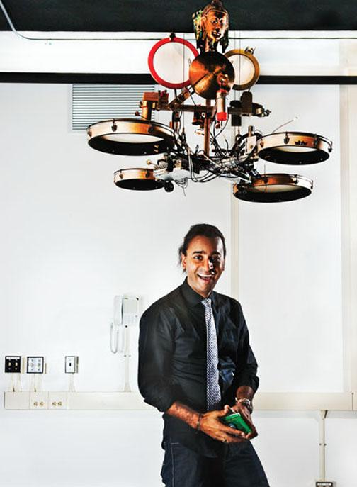 Ajay Kapur '02, a professor at the California Institute of the Arts, develops robotic instruments. He stands beneath MahaDeviBot, which strikes 12 percussion instruments from India. The bouncing head can relay tempo to the human performer.