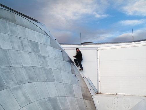 In the Atacama Desert in northern Chile, professor Suzanne Staggs *93 climbs to the top of the Atacama Cosmology Telescope to inspect a sensor.