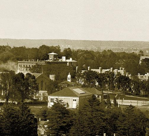 Marking the home of University president John Grier Hibben 1882, the Prospect House tower rises over the Brown Hall dorm, with brand-new Cuyler dorm, with its many chimneys, at right. Below the little white cupola of Brokaw Memorial pool is the barnlike C