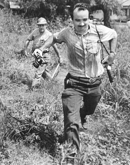 A sheriff's deputy pursues Matt Herron '53 during a march in Philadelphia, Miss., in 1966.