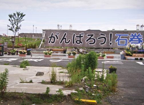 """A brightly painted sign in a heavily damaged area reads, """"Let's do our best – we can do it, Ishinomaki!"""""""
