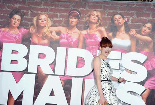 "Kemper won raves for her comedic role in the feature film ""Bridesmaids."" Here, she walks past the movie poster as she arrives at the premiere in Los Angeles in April."