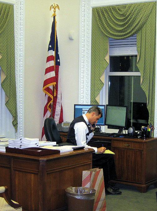 Dressed for a White House party, Alan Krueger works on statistics needed for a 2011 presidential speech.