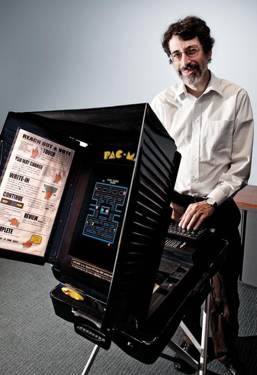 Professor Andrew Appel '81 with a symbol of the center's work: a voting machine turned into a Pac-Man game.
