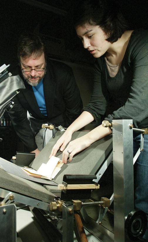 Clifford Wulfman and Erika Eggleston scan a handwritten book of poems by Russian writer Osip Mandelstam so that it can be viewed online; they use a special cradle that ensures the process will not damage the book's spine.
