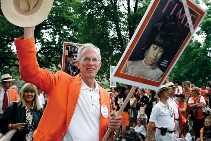 """Henry """"Hank"""" Bone '68 tips his hat to onlookers along the P-rade route."""