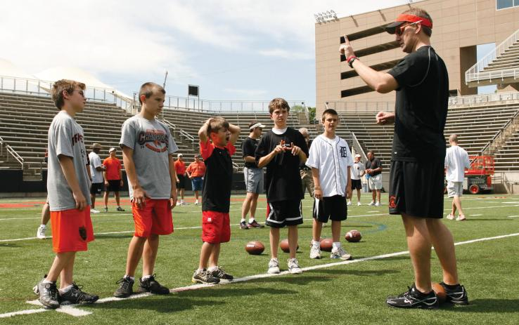 Wide receivers coach Scott Sallach conducts a football clinic with, from left: Andrew and Jackson (sons of Steve Simcox '83), Manny (son of Luis Castro '88), Rhodes (son of Wit Hall '88), and Sam (son of Greg Stevens '88)