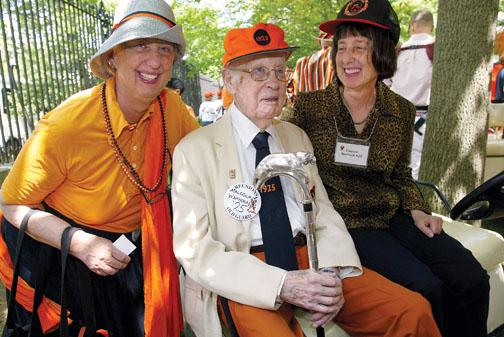 For the fifth time, Malcolm Warnock '25, with his daughters, Margaret Carlough, left, and Eleanor Warnock, carries the silver-topped Class of 1923 Cane.