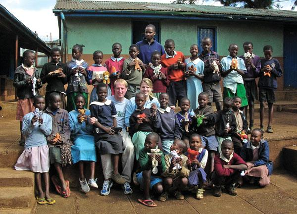 Hunter Woolley '98 and Ann Ellis Woolley '01, center, with students at the RAFIKI school in Kibera, Kenya.