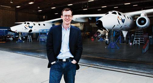 George Whitesides '96, stands in front of a hangar with WhiteKnight Two, or Eve, the mother ship for SpaceShip Two.