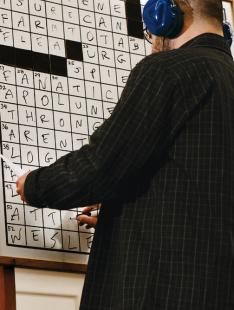 Wearing noise-canceling headphones, Dan Feyer '99 finishes his puzzle to win the national crossword competition in March.