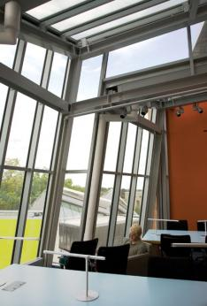 From this study area on the top level, students can take in the stainless-steel roof and different shapes of the building visible outside, and the campus beyond.